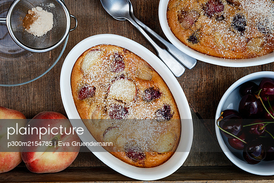 Bowls of gluten free homemade clafoutis with cherries, peaches and almonds - p300m2154785 by Eva Gruendemann