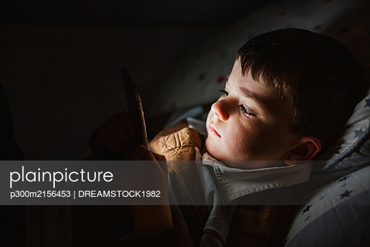 Portrait of little boy lying in bed using smartphone at night - p300m2156453 by DREAMSTOCK1982