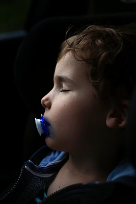 Young boy sleeping in a car - p1028m2109008 by Jean Marmeisse