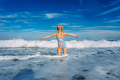 Rear view of girl with arms outstretched standing in sea against cloudy sky - p1166m1509363 by Cavan Images