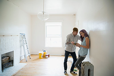 Couple using cell phone in empty new house - p1192m1158277 by Hero Images