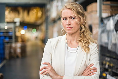 Portrait of confident woman in factory storehouse - p300m2059916 by Daniel Ingold