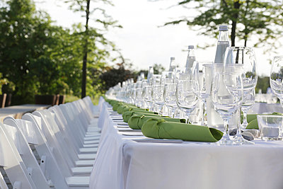 Festive laid table with green napkins and wine glasses - p300m911308f by Jan Tepass