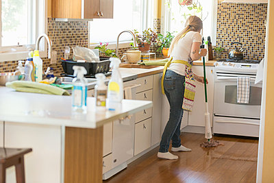 Young woman mopping with green cleaning products - p924m973850f by heshphoto