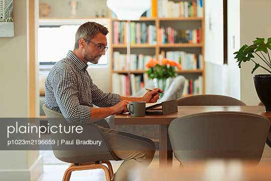 Businessman using digital tablet, working from home at dining table - p1023m2196659 by Paul Bradbury