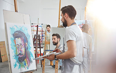 Male artists painting at easel in art class studio - p1023m1506501 by Agnieszka Olek
