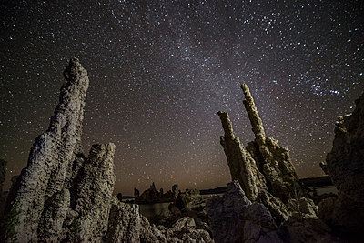 Low angle majestic view of Tufa against star field - p1166m1526596 by Cavan Images