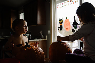 two kids Pumpkin carving at halloween in their home - p1166m2269343 by Cavan Images