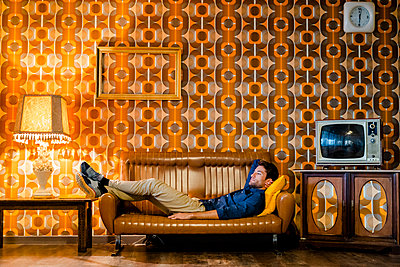 Man lying on couch in vintage living room - p300m2070600 by Giorgio Fochesato