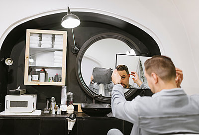 Customer checking his haircut in mirror at barber shop - p300m2113986 by Hernandez and Sorokina