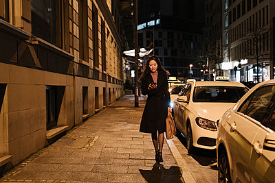 Young woman walking and using smartphone in the city at night, Frankfurt, Germany - p300m2188130 by Hernandez and Sorokina