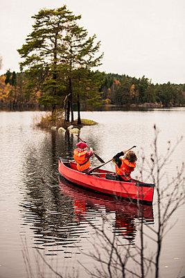 Siblings canoeing on river - p426m766586f by Katja Kircher