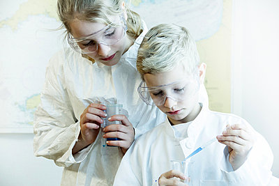 Brother and sister wearing safety goggles doing science experiment - p429m803670f by Sigrid Gombert