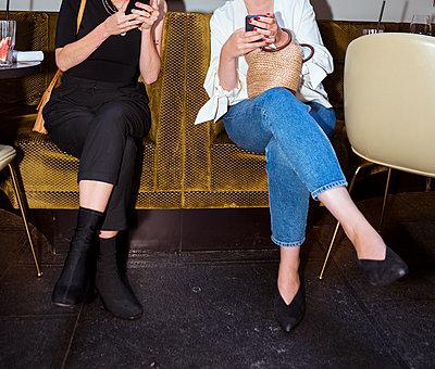 Zwei Frauen schauen auf ihr Handy - p432m1586084 von mia takahara