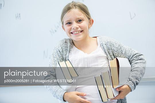 Portrait of happy schoolgirl carrying books in class - p300m2005281 von Fotoagentur WESTEND61