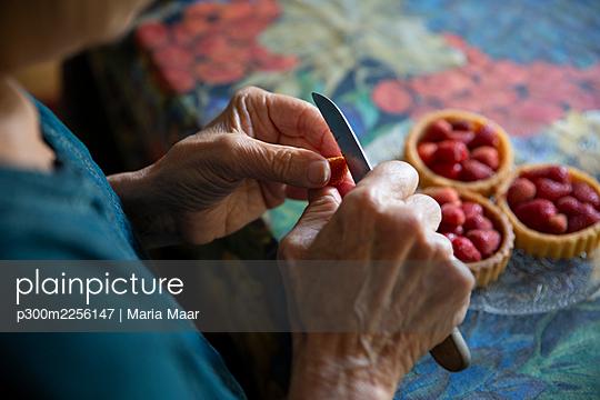 Senior woman preparing strawberry tarts - p300m2256147 by Maria Maar