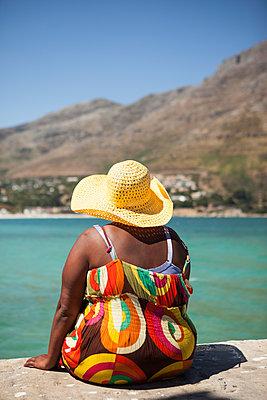 Afrikanerin sitzt am Hafen - p045m1220895 von Jasmin Sander