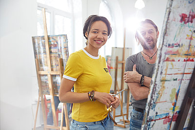 Portrait smiling artists painting at easel in art class studio - p1023m1506489 by Agnieszka Olek