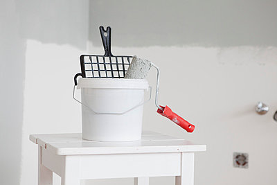 Paint bucket and roll on white table - p300m1047559f by Rainer Berg