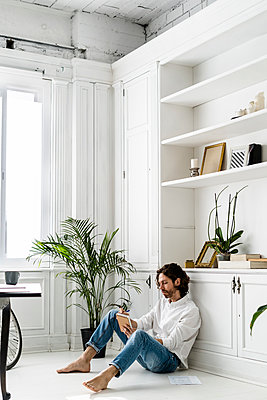 Man sitting on the floor at home taking notes - p300m2143752 by Giorgio Fochesato