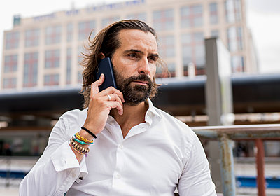Candid portrait of bearded businessman sitting outdoors and talking on smart phone - p300m2240869 by Jose Carlos Ichiro