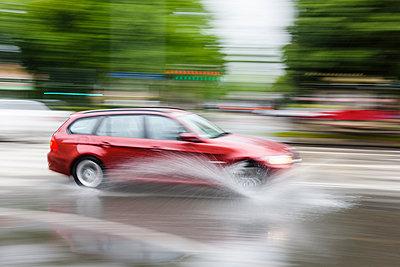 Car splashing water on road - p312m1103620f by Mikael Svensson