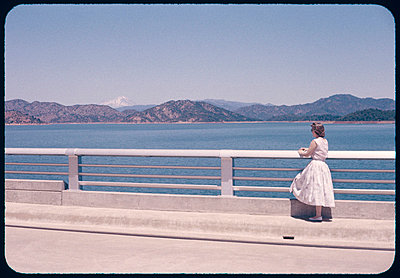 Woman in dress stands on bridge circa 1950s - p3720629 by James Godman