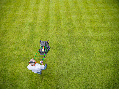 Man wearing headphones and mowing lawn - p429m726946f by Monty Rakusen