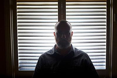 Man standing by a window - p584m710279 by ballyscanlon