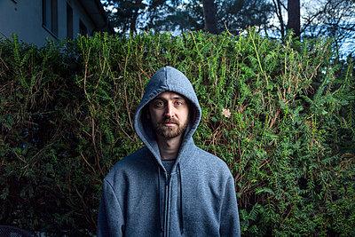 Junger Mann im Kapuzenshirt vor einer Hecke - p975m2172253 von Hayden Verry