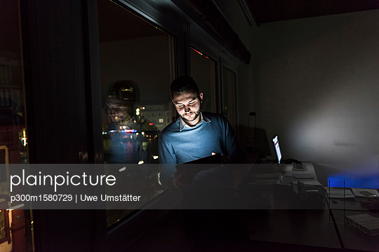 Businessman sitting on window sill in office at night using tablet - p300m1580729 von Uwe Umstätter