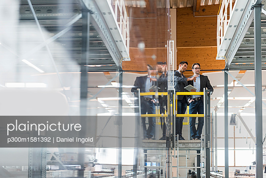Two businessmen with tablet talking in modern factory - p300m1581392 von Daniel Ingold