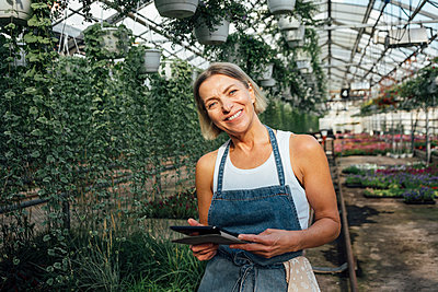 Smiling female agriculture worker holding digital tablet at plant nursery - p300m2300060 by Vasily Pindyurin
