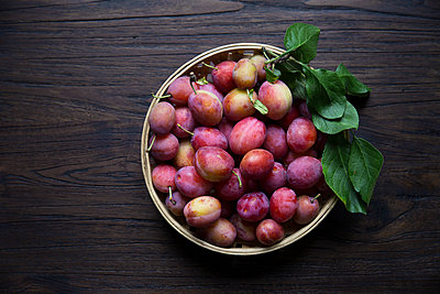 Directly above shot of peaches in basket on wooden table - p426m1196502 by Sonja Dahlgren