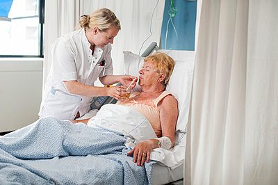 Nurse helping patient in hospital bed take a drink - p429m1197779 by Arno Masse