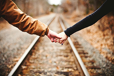 Close up of couple holding hands on railroad tracks - p555m1408971 by Shestock