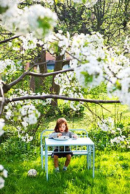 Boy eating cherries in the garden - p972m1160313 by Berno Hjälmrud