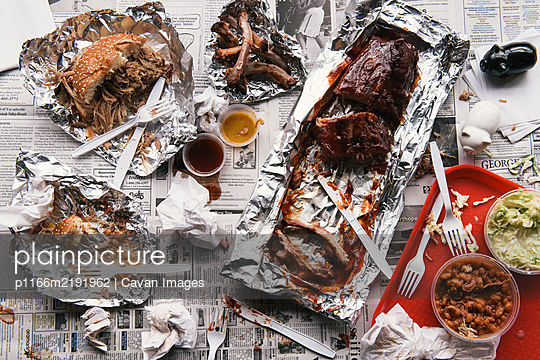 Messy barbecue of ribs and pulled pork sandwich half eaten - p1166m2191962 by Cavan Images