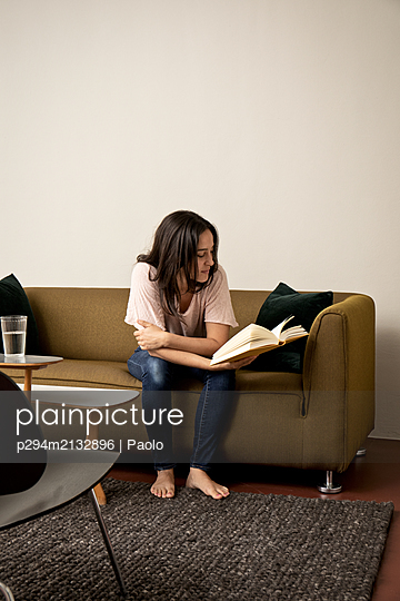Brunette woman on sofa reading book - p294m2132896 by Paolo