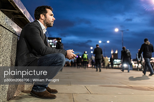 UK, London, thoughtful businessman in the city by night - p300m2069706 by William Perugini
