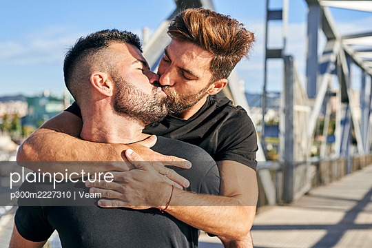 Gay man kissing boyfriend on footbridge during sunny day - p300m2227310 by Veam