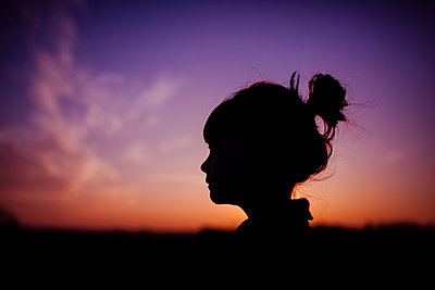 Silhouette girl against dramatic sky during sunset - p1166m1176225 by Cavan Images