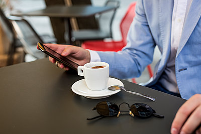 Close-up of businessman using cell phone in a cafe - p300m1166234 by Mauro Grigollo