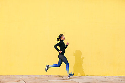 Spain, Barcelona, jogging woman in front of yellow wall - p300m1188489 by Bonninstudio