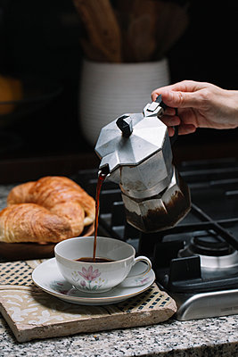 Cropped hand of mature woman pouring coffee in cup on kitchen counter at home - p300m2197286 by Alberto Bogo