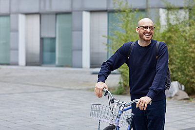 Smiling man standing with bicycle on street - p300m2214044 by Maya Claussen