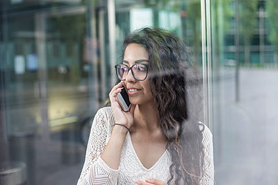 Close-up of woman with long hair talking over mobile phone while standing against window - p300m2220530 by Bernd Friedel