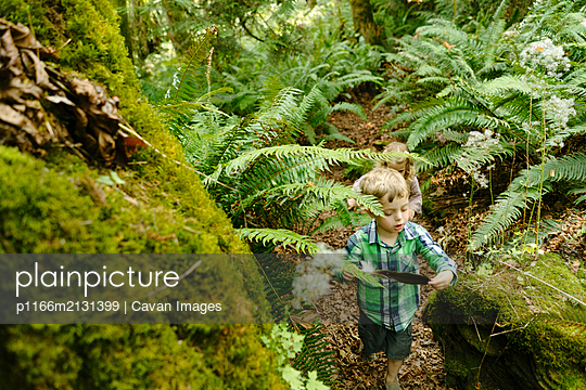 View from above of a young boy hiking through the trees with a feather - p1166m2131399 by Cavan Images