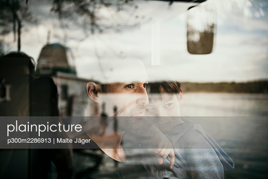 Father and son seen through glass window - p300m2286913 by Malte Jäger