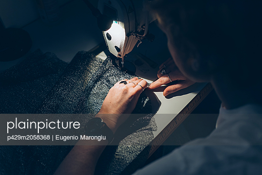 Woman working late at sewing machine - p429m2058368 by Eugenio Marongiu
